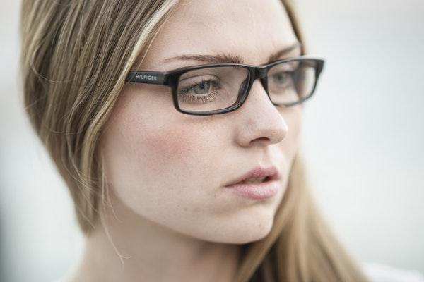 Portret młodej kobiety, noszącej okulary.